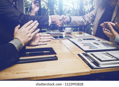 Shaking hands of business lawyer of tax and real estate broker after meeting in conference room, all people happy successfully.