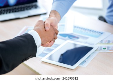 Shaking hands at a meeting. Two Confident businessman sitting at the negotiating table in the office and shaking hands close-up view of hands. Business people dressed in formal wear