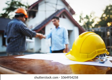 Shaking hands of partnership agreement between structural engineers and contractors to build houses. After agreeing the employment price and calculating the cost of construction and repair real estate