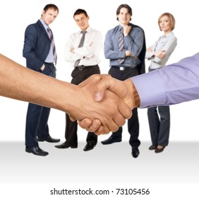 Shaking hands of two businessmen against four businesspeople standing in the background