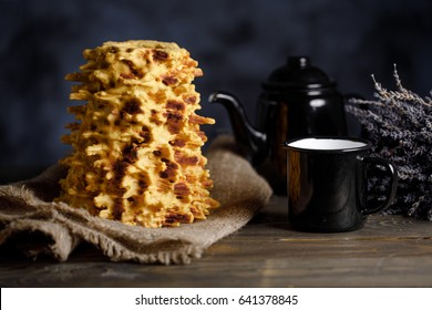 Shakotis is a national Lithuanian baking. Black kettle and cup on the table on a black background.