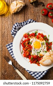 Shakshouka, dish of eggs poached in a sauce of tomatoes, chili peppers, onions. Top view.