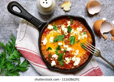 Shakshouka (spicy tomato stew with chicken eggs) with feta cheese - traditional dish of israeli cuisine in a black cast iron pan over light slate, stone or concrete background.Top view.