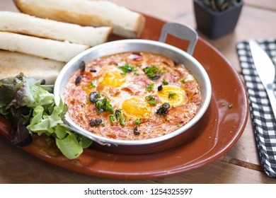 Shakshouka. Shakshouka is a Tunisian and Israeli dish containing of tomatoes, onions, pepper, spices, and eggs. It is sometimes called shakshuka or chakchouka. Generally served for breakfast.