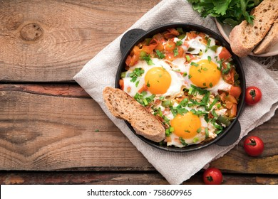 Shakshuka with eggs, tomato, and parsley in a iron pan. Shakshuka - traditional israeli tomato stew with eggs .
