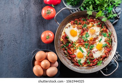 Shakshuka in a frying pan. Middle eastern traditional dish with fried eggs,  tomatoes, bell pepper, vegetables and herbs.. Top view