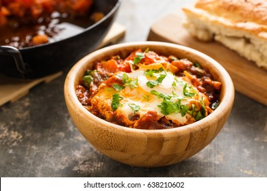 Shakshuka with herbs served in a wooden bowl