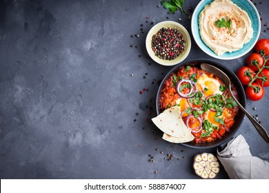 Shakshuka with pita bread in pan, hummus in bowl on rustic background. Middle eastern traditional dishes. Fried eggs with vegetables. Top view. Space for text. Middle eastern style breakfast or lunch