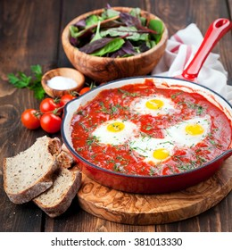 Shakshuka with tomatoes and eggs in a cast iron pan, selective focus