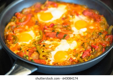 shakushuka a savory egg meal cooking in a frying pan. It contains peppers, tomatoes, eggs, onions and spices. It is a middle eastern dish.