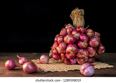 Shallot onions in a group on a wooden table in the dark background.Shallots are ingredients in Thai curry.Shallots are Thai food and Thai herbs.Shallots are food that nourishes blood.