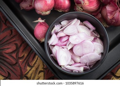 Shallots (Red Onion) in black bowl on old wooden table and shallots bunch background . selective focus
