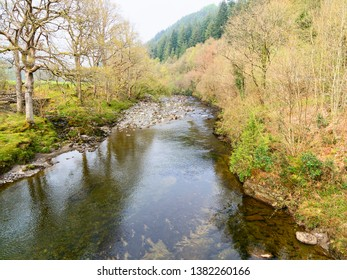 The shallow, clear, River Mawddach in Gwynedd, Wales, flows gently over rocks and between banks lined with rees and fields.