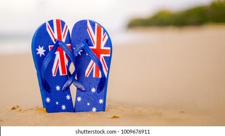 Shallow depth of field Australian flag thongs/flip-flops washed up on a sandy beach