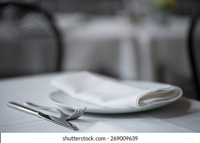 Shallow depth of field close up of knife, fork, plate and folded napkin laid upon white table cloth at elegant restaurant.