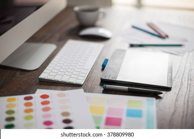 Shallow depth of field closeup of a graphic designer's workspace with a pen tablet, a computer and some color swatches