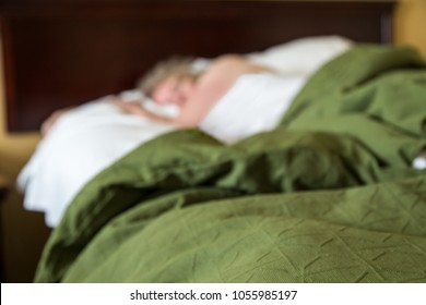 shallow depth of field focus on the bed in the foreground, a generic woman sleeps in background