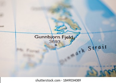 Shallow depth of field focus on geographical map location of Mount Gunnbjorn Fjeld in Greenland North America continent on atlas