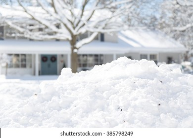 shallow depth of field focused on pile of snow with the house in background
