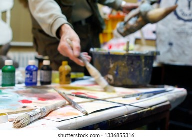 Shallow depth of field on brushes and artist painting in the background