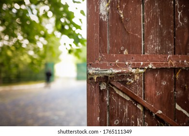 Shallow depth of field (selective focus) image with an old and unused metal latch on a wooden gate.