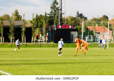 Shallow depth of field shot of group of male soccer players playing amateur soccer match on sunny summer day on simple sports venue in Denmark.