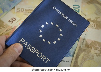 Shallow depth of field shot of man an holding European Union passport against backdrop of euro notes