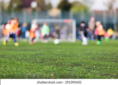 Shallow depth of field shot of young boys playing a kids football match on green turf.