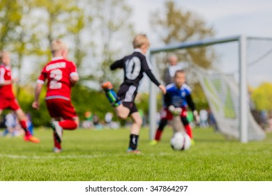 Shallow depth of field shot of young boys playing a kids soccer match on green grass.