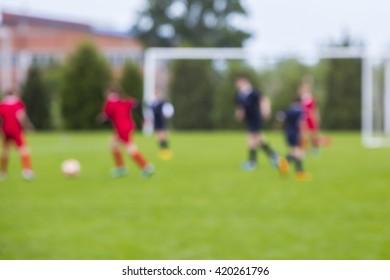 Shallow depth of field shot of young boys playing a kids european football match on green grass.