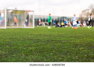 Shallow depth of field shot of young boys playing a kids soccer match on green turf.