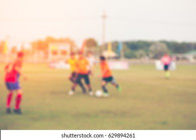 Shallow depth of field shot of young boys playing a kids soccer match on green turf