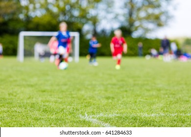 Shallow depth of field shot of young boys playing a kids european football match on green grass.