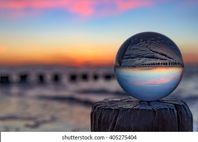 Shallow depth of field sunset in pastel colors with a glass globe at the beach