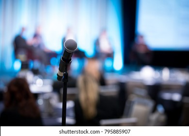 Shallow depth of field view of a microphone on a stand, with blurry panel of guest speakers on stage, at a shareholder conference