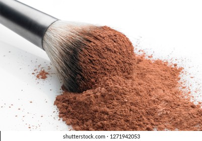 Shallow depth of focus. Close up view of a makeup brush over a pile of cosmetic powder. White background