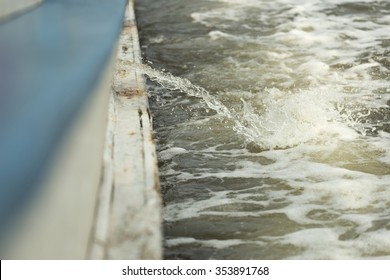 Shallow DOF of bilge being pumpt out of boat splashing into sea while boat is moving