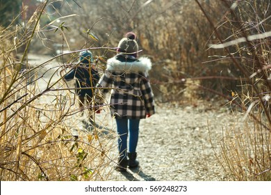 shallow DOF of brother and sister siblings walking together in woods during wintertime