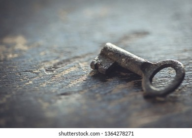 Shallow DOF.Antique worn out key on a wooden background.