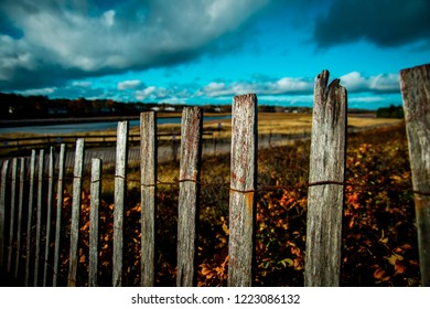 A shallow focus center shot of rusted and rustic wooden sea fence separating the marshland from ocean in Maine against a cloudy blue fall sky.