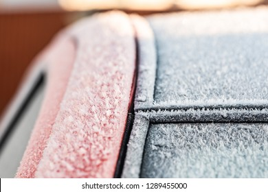 Shallow focus, detailed view of a heavily frosted car windscreen and panoramic roof seen during mid winter. The car will soon be defrosted before it is safe to drive.
