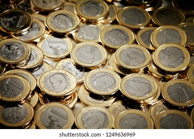 Shallow focus on heap of one euro coins. Focus light in the center of image.