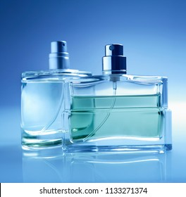 Shallow focus on two perfume bottles.Focus on foreground bottle.General cool blue tone.