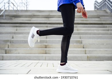 A shallow focus of a person in sportswear jogging in a park in the morning