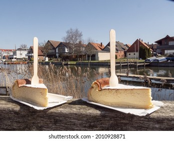 A shallow focus shot of 2 cheesecake pieces with fork stuck in them in front of the Steinhuder Meer in Germany - Shutterstock ID 2010928871