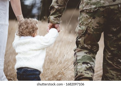 A shallow focus shot of an American soldier with his wife holding their child