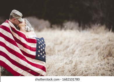 A shallow focus shot of an American soldier kissing his loving wife while wrapped in an American flag