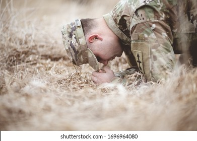 A shallow focus shot of an American soldier kneeling and praying on a dry grass field