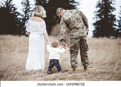 A shallow focus shot of an American soldier and his lovely wife holding their baby's hands while walking on a dry grass field