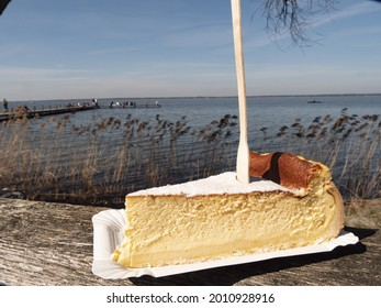 A shallow focus shot of a cheesecake piece with fork stuck in it in front of the Steinhuder Meer in Germany - Shutterstock ID 2010928916